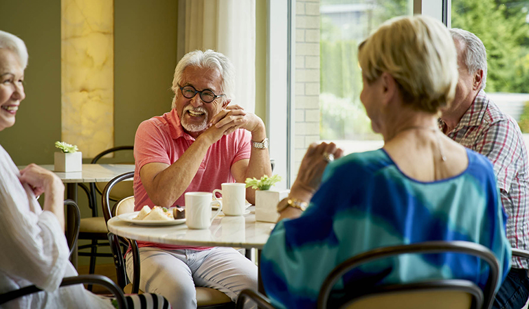Residents socializing around a bistro table