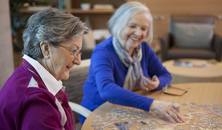 Two residents working on a jigsaw puzzle