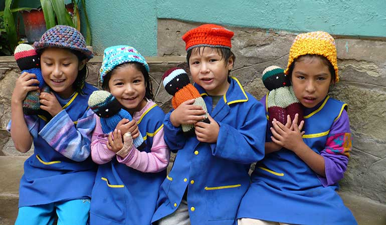 Children holding comfort dolls
