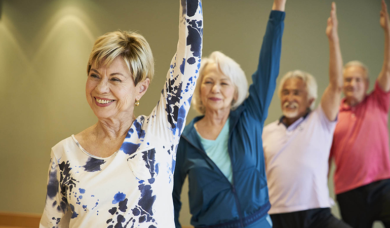 Residents with arms raised in a yoga class