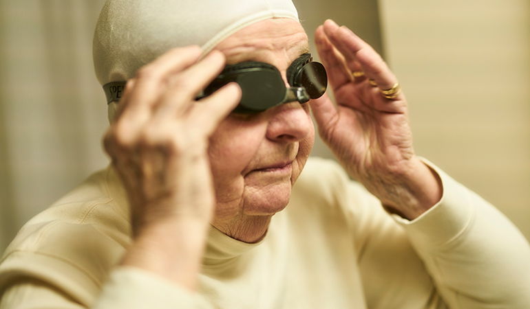 Summerhill PARC resident Peggy putting on swim goggles
