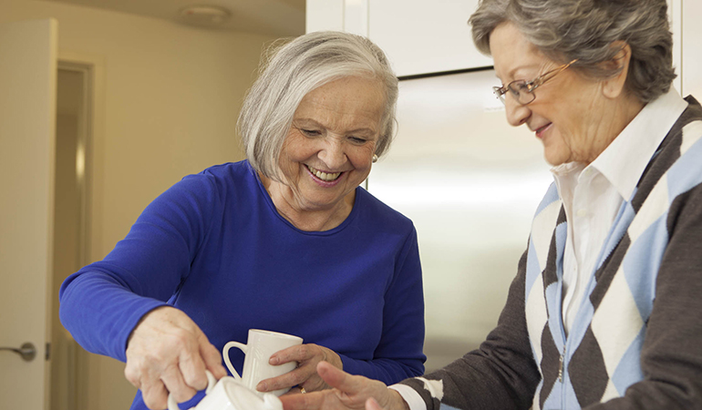 Two residents pouring tea