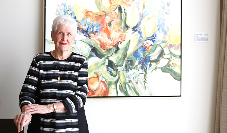 Westerleigh PARC resident Bette in front of floral painting