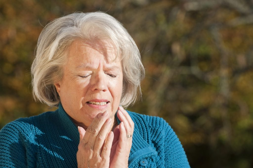 Senior woman sneezing into her hands
