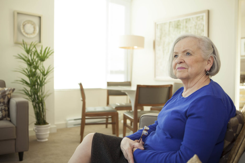 Senior woman sitting in her suite