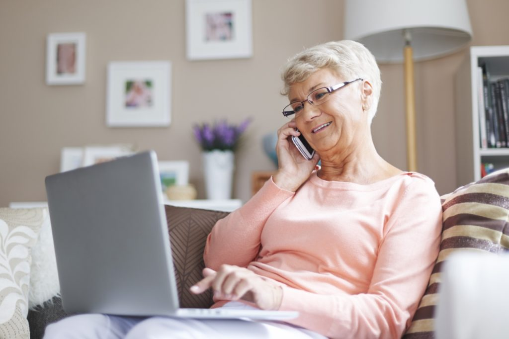 Senior woman smiling and using laptop and phone