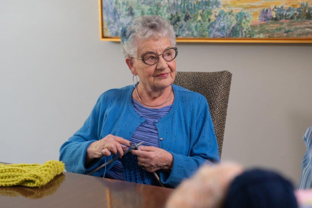 Cedar Springs PARC resident Cathy knitting