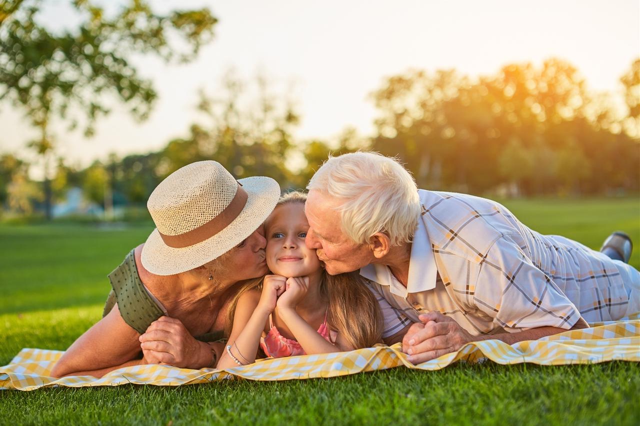 Seniors kissing grandchild