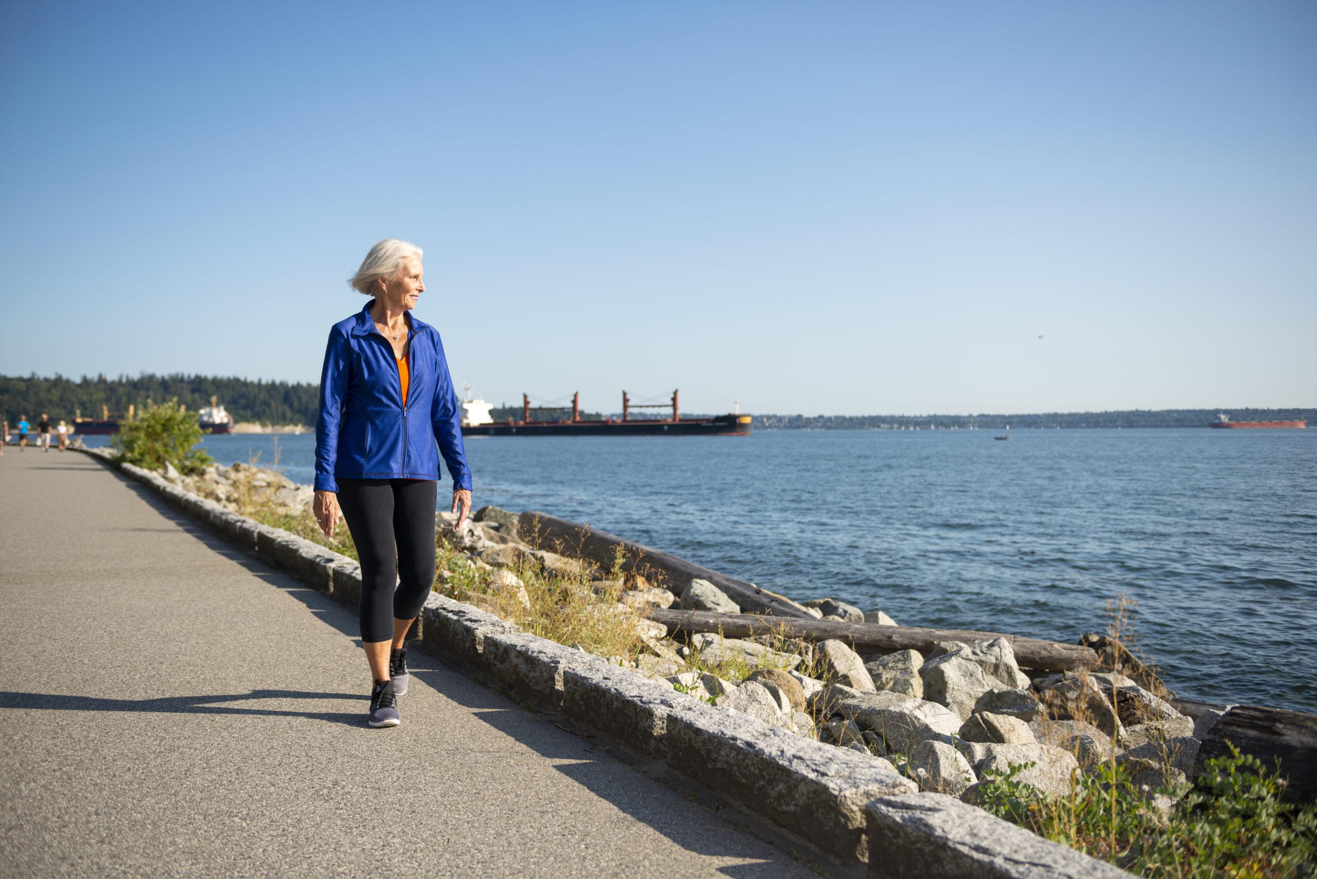 Senior woman walking along seawall