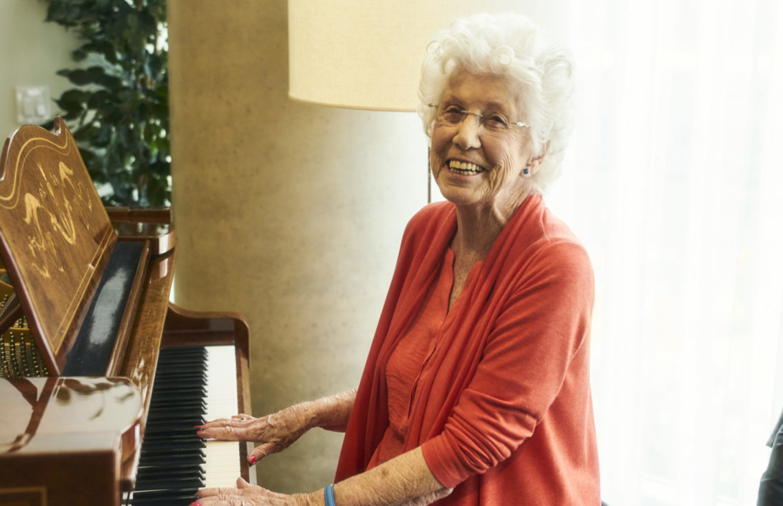 Westerleigh PARC resident Dorothy smiling and playing the piano