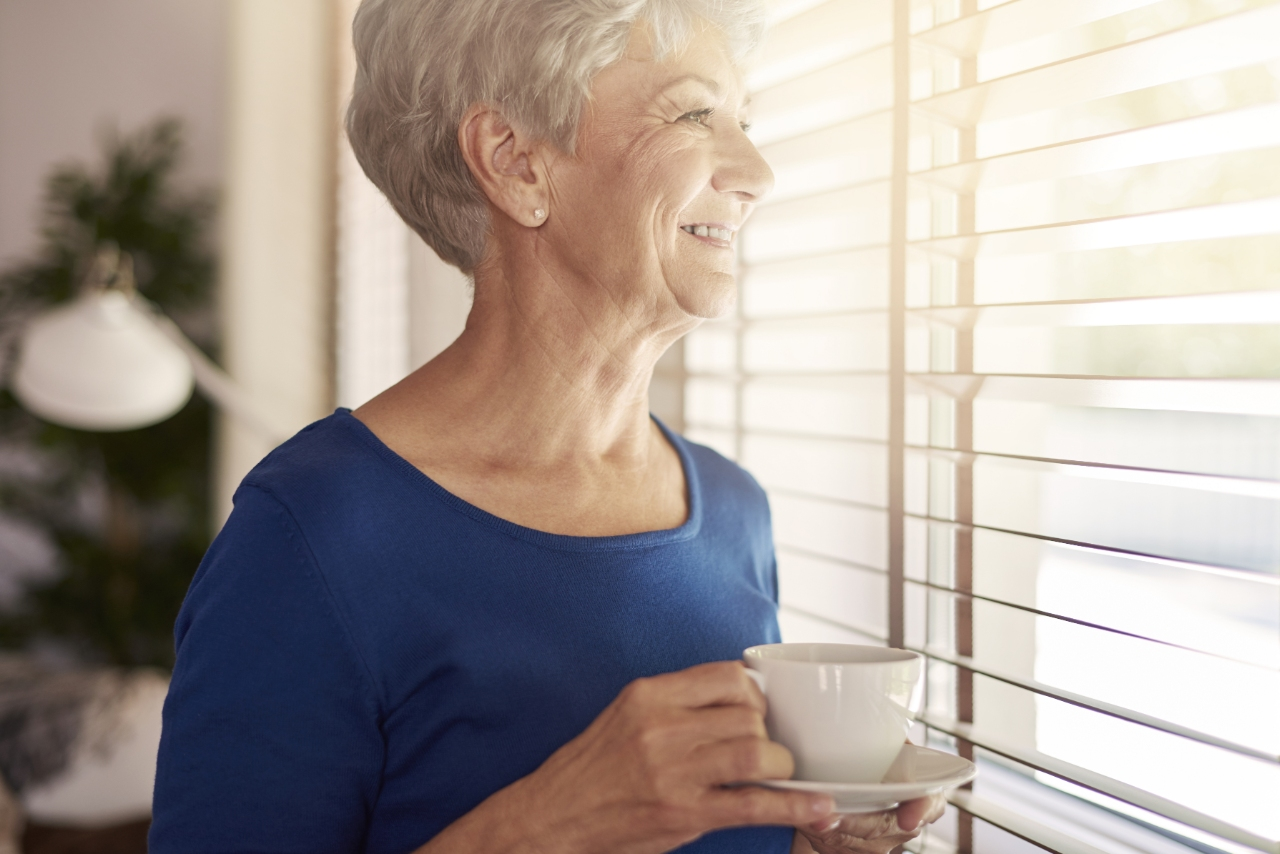 senior woman smiling looking out the window with cup of coffee