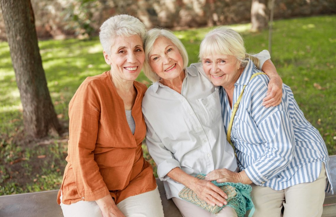 Three senior women happily holding each other