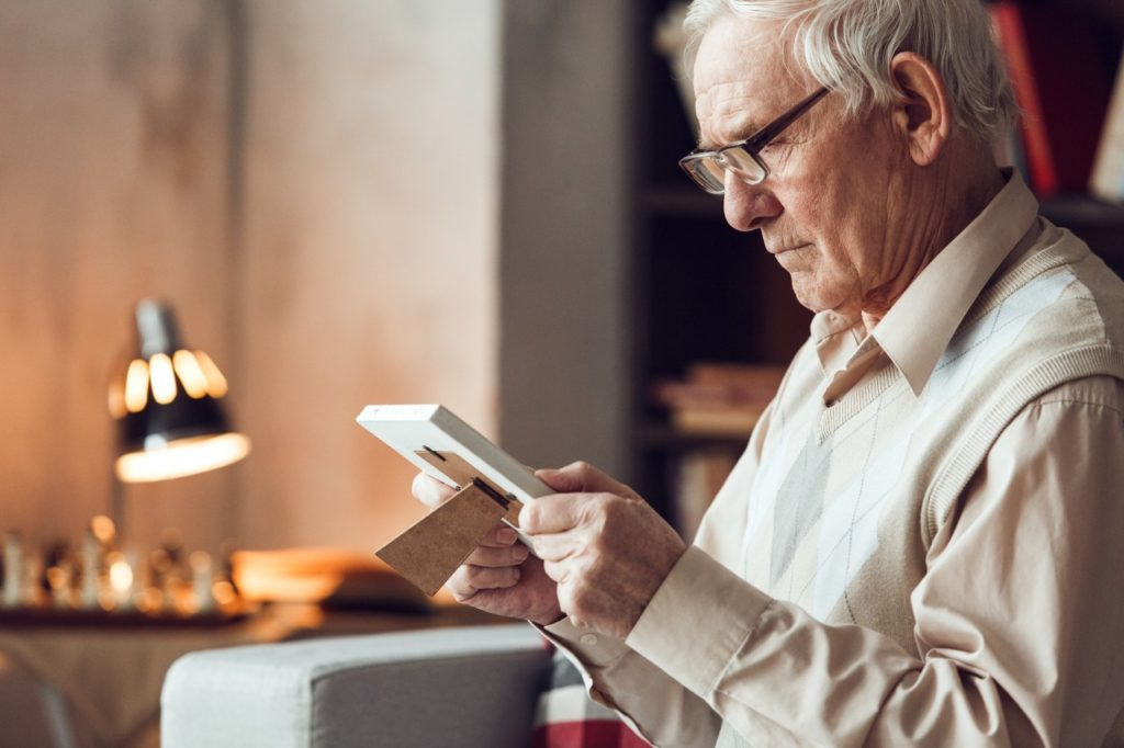 Senior man looking at photo frame
