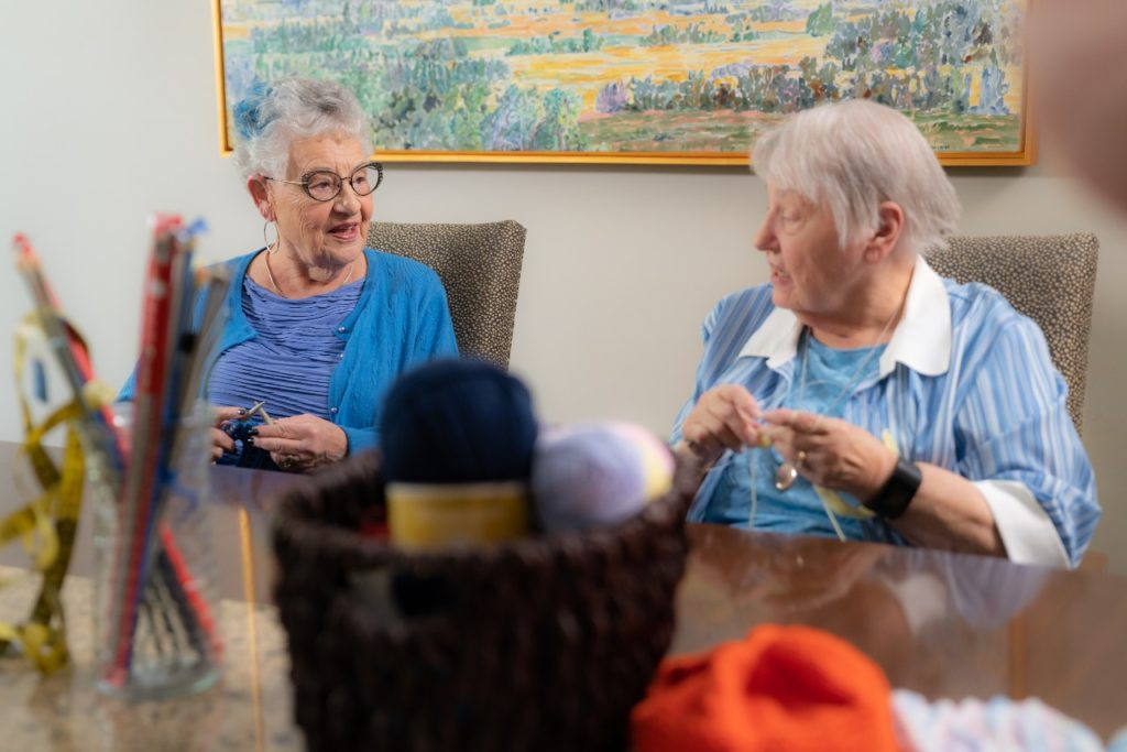 Two senior ladies knitting together